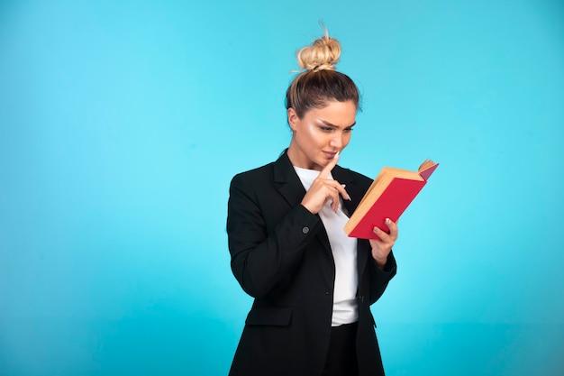 Mulher de negócios no blazer preto com um livro vermelho e lendo-o.