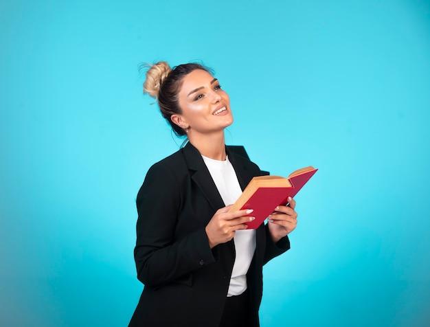 Mulher de negócios no blazer preto com um livro vermelho pensando.