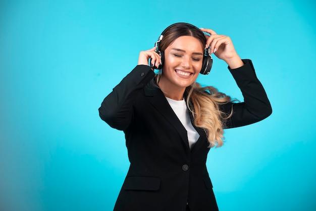 Mulher de negócios no blazer preto usando fones de ouvido.