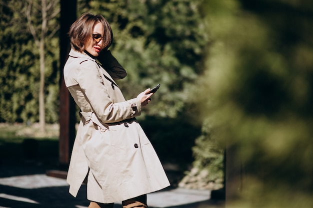 Mulher de negócios no casaco usando telefone fora