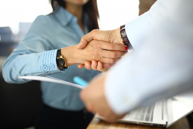 Mulher de negócios no escritório agita as mãos com homem