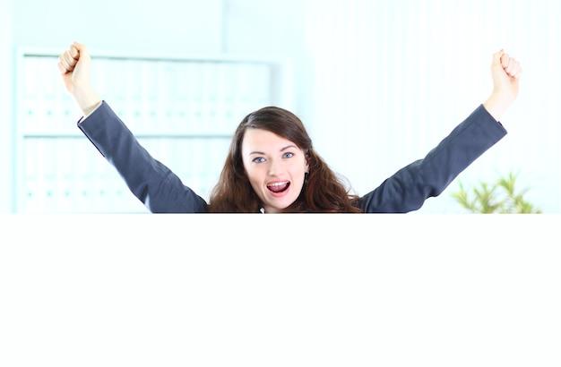 Mulher de negócios no escritório do cartaz de programas, mãos ao alto.