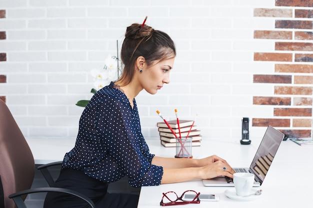 Mulher de negócios no escritório uma mesa com o laptop
