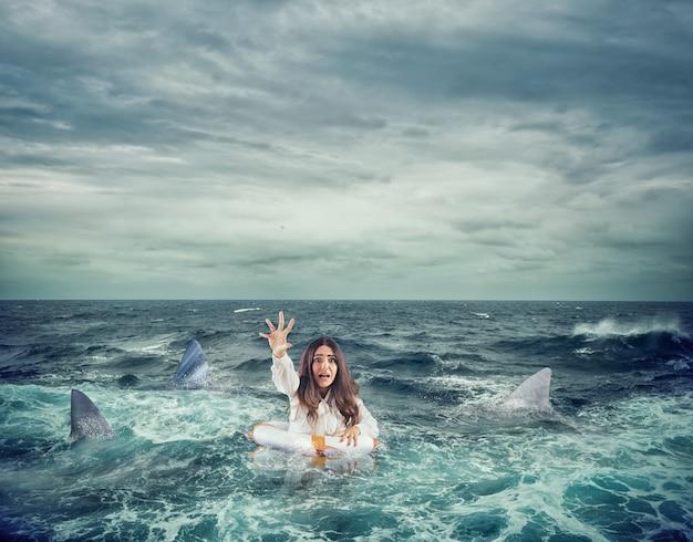 Mulher de negócios no oceano com salva-vidas rodeada de tubarões pede ajuda