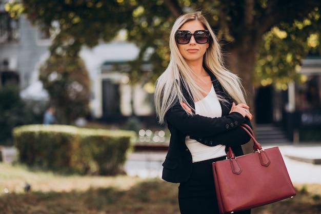 Mulher de negócios no parque com bolsa vermelha