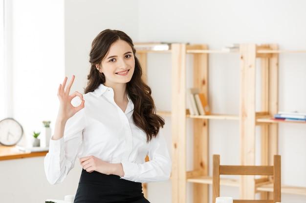 Mulher de negócios no vestuário formal que guarda originais e que mostra o sinal aprovado no escritório moderno, espaço da cópia.