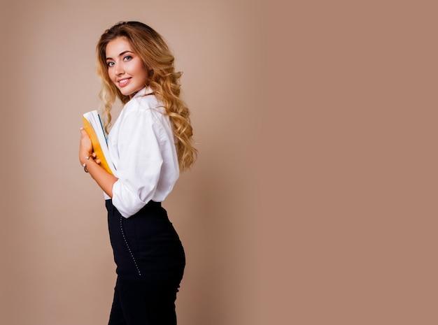 Mulher de negócios nos monóculos à moda que estão sobre a parede bege. cabelos ondulados loiros. blusa branca e calça preta.