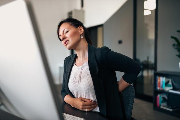 Mulher de negócios nova bonita que tem a dor nas costas ao sentar-se na mesa de escritório.