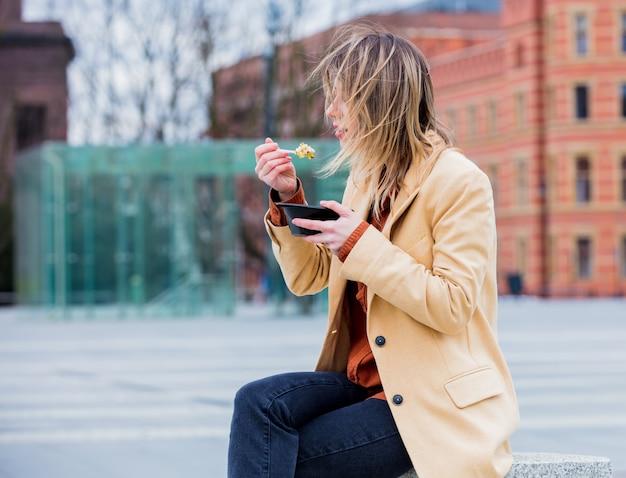 Mulher de negócios nova com salada na cidade urbana ao ar livre.