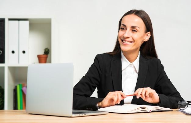 Mulher de negócios nova feliz que senta-se atrás da mesa com livro; caneta e laptop