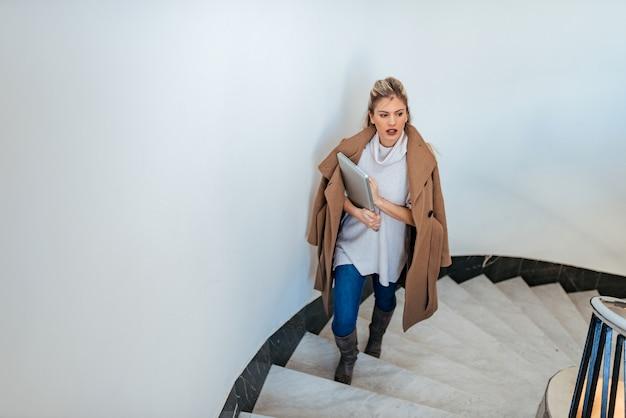 Mulher de negócios nova que anda acima das escadas.