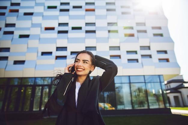 Mulher de negócios nova que fala no telefone celular durante a ruptura de café exterior, perto do prédio de escritórios.