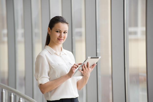 Mulher de negócios nova que fala no telefone móvel ao estar pela janela no escritório. bela jovem modelo feminino em um escritório brilhante.
