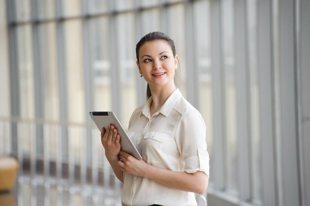 Mulher de negócios nova que fala no telefone móvel ao estar pela janela no escritório. bela jovem modelo feminino no escritório.