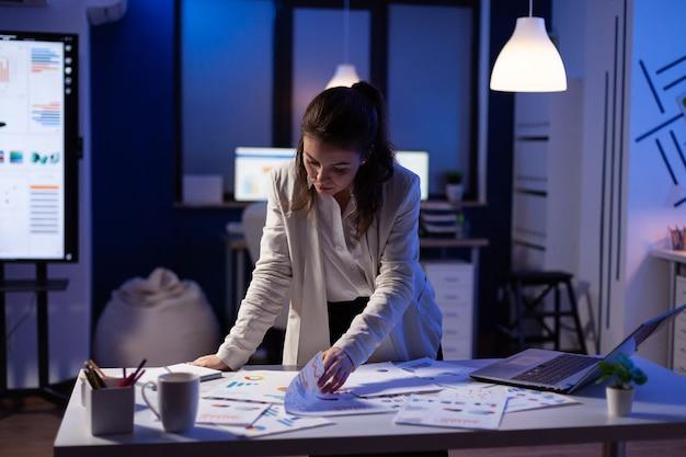 Mulher de negócios ocupada trabalhando em relatórios financeiros, verificando os números para a reunião executiva. gerente exausto trabalhando com estatísticas econômicas no escritório da empresa tarde da noite