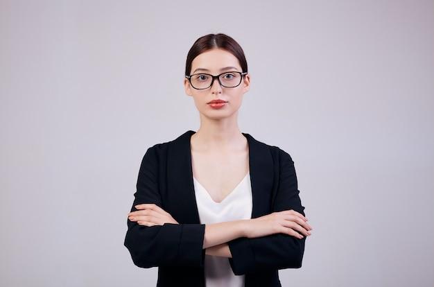 Mulher de negócios olhando direto e está de pé em cinza em uma jaqueta preta, camiseta branca e óculos de computador. a mão da mulher segura a borda da jaqueta.