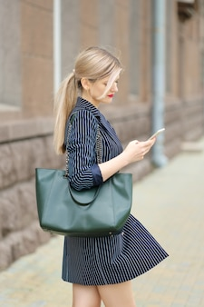 Mulher de negócios olhando o celular na rua.