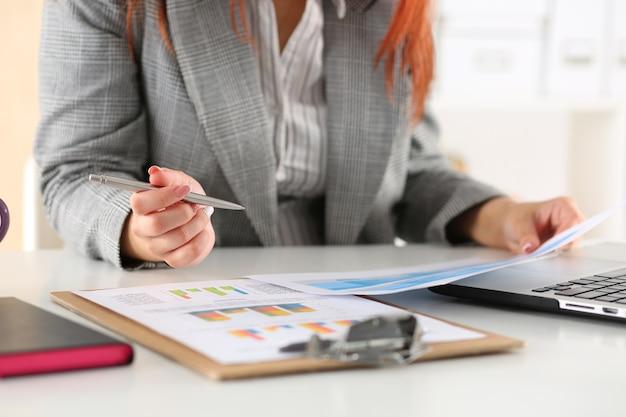 Mulher de negócios olhando para gráficos. relatórios de leitura do gerente ou auditor. planejamento financeiro, análise de negócios e conceito de gerenciamento de projetos.