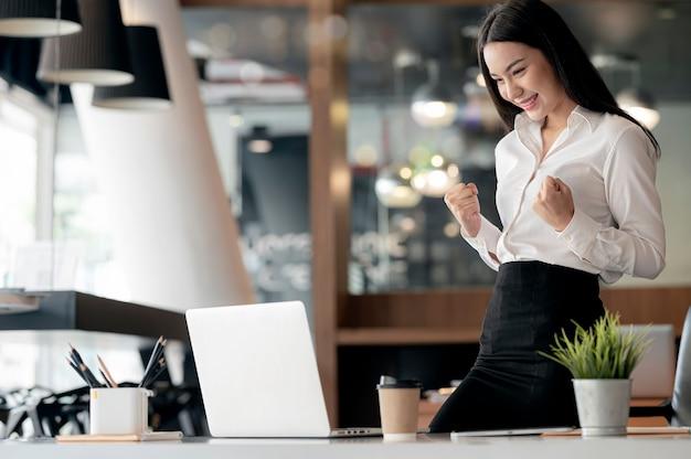 Mulher de negócios olhando para o laptop e mãos ao alto de felicidade no sucesso enquanto estava no escritório.