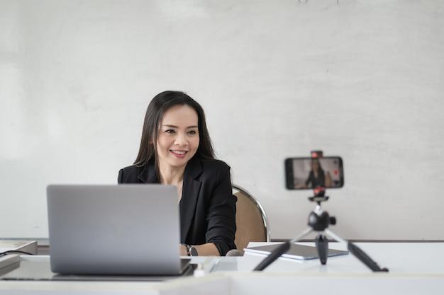 Mulher de negócios ou professor tutor do sudeste asiático fazem videoconferência em um laptop
