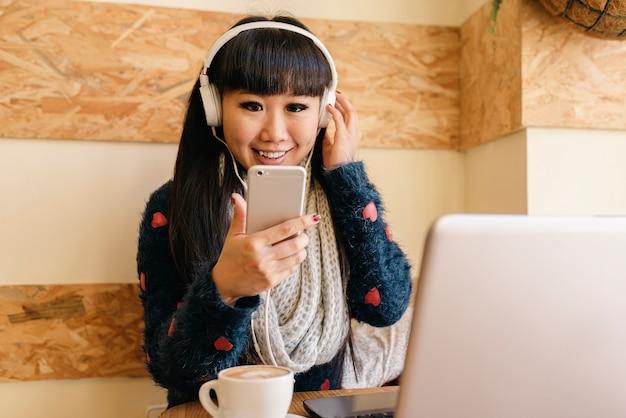 Mulher de negócios ouvindo música na cafeteria. conceito de negócios