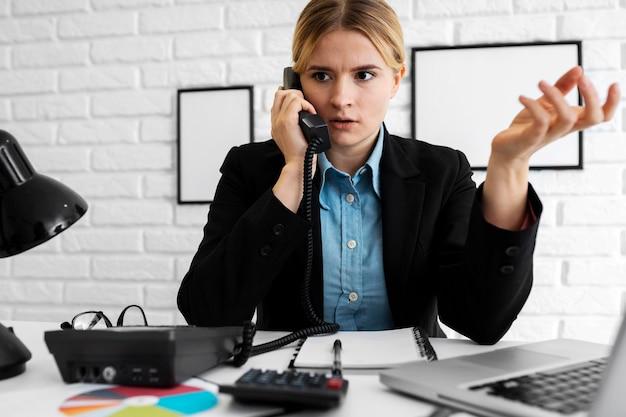 Mulher de negócios parecendo irritada enquanto fala ao telefone
