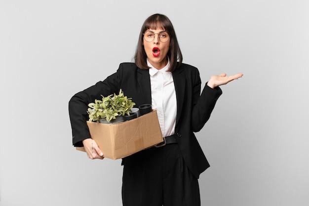 Mulher de negócios parecendo surpresa e chocada, com o queixo caído segurando um objeto com a mão aberta na lateral