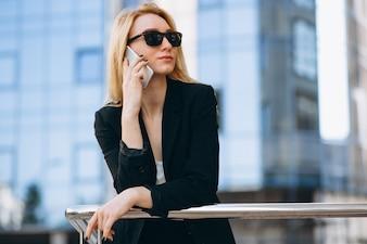 Mulher de negócios pelo arranha-céu usando o telefone