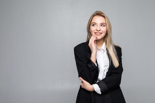 Mulher de negócios pensativa com um dedo sob o queixo que olha isolado.