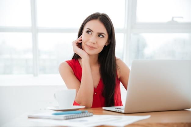 Mulher de negócios pensativa de camisa vermelha, sentada junto à mesa com uma xícara de café, documentos e laptop. janela no fundo