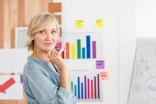 Mulher de negócios pensativa escrevendo em um quadro branco