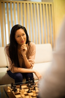 Mulher de negócios pensativa jogando xadrez com um colega