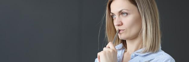 Mulher de negócios pensativa segura a caneta e analisa o desenvolvimento de pequenas e médias empresas