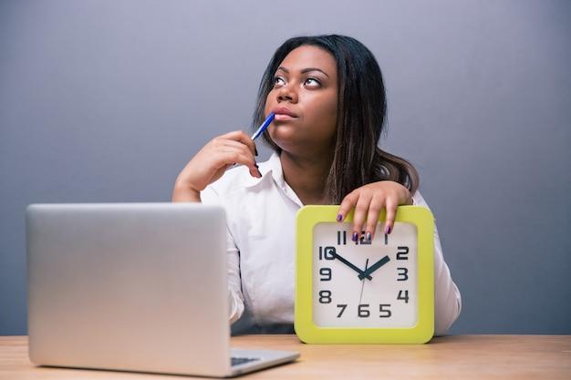 Mulher de negócios pensativa sentada à mesa no escritório