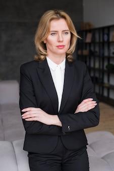 Mulher de negócios pensativo em pé com os braços cruzados