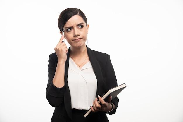 Mulher de negócios posando com caderno e lápis na parede branca.