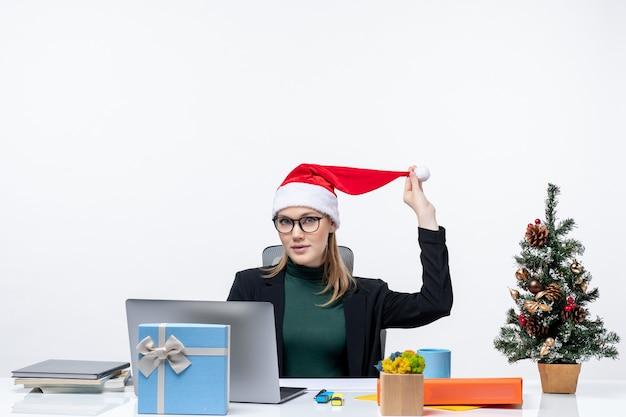 Mulher de negócios positiva brincando com um chapéu de papai noel, sentada à mesa com uma árvore de natal e um presente nela e verificando seus e-mails no fundo branco