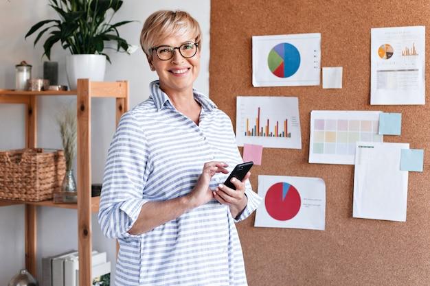 Mulher de negócios positiva com camisa listrada segurando smartphone