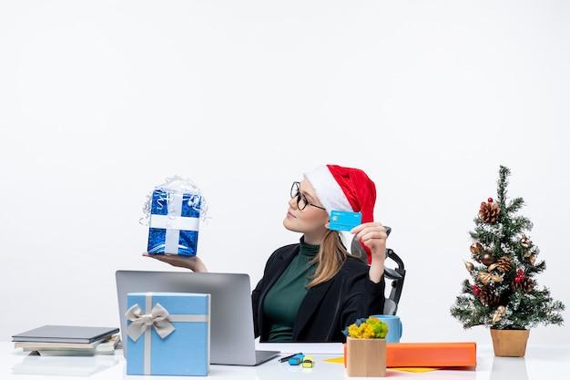 Mulher de negócios positiva com chapéu de papai noel e usando óculos, sentada em uma mesa segurando um presente de natal e um cartão de banco na imagem de estoque do escritório
