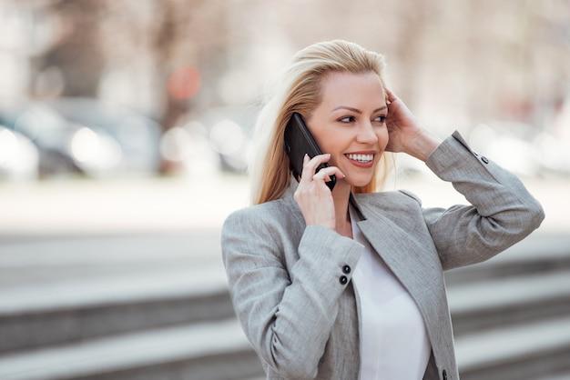 Mulher de negócios positiva no vestuário formal que fala no telefone na cidade na primavera.
