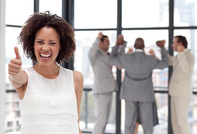Mulher de negócios positiva que faz um thum-up com seus colegas