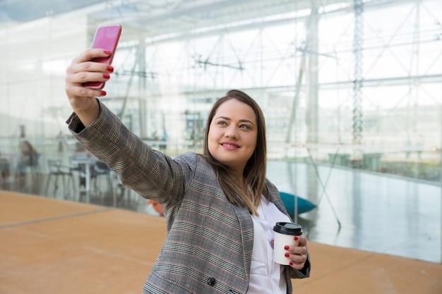 Mulher de negócios positivo, tirando foto de selfie no telefone ao ar livre