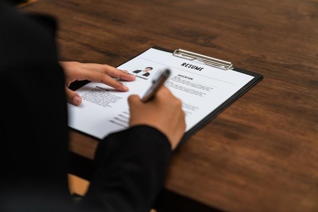 Mulher de negócios preenche informações de inscrição de currículo na mesa