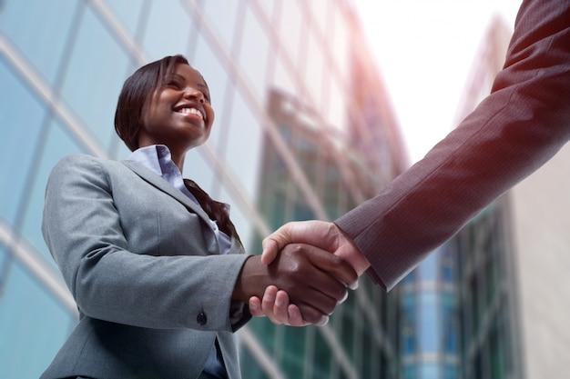 Mulher de negócios preto jovem apertando as mãos com um homem de negócios