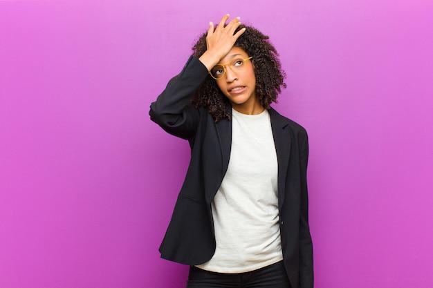 Mulher de negócios preto jovem levantando a palma da mão na testa pensando opa, depois de cometer um erro estúpido ou lembrar, sentindo-se burro