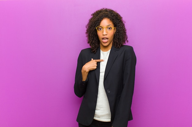 Mulher de negócios preto jovem olhando chocado e surpreso com a boca aberta, apontando para si mesmo