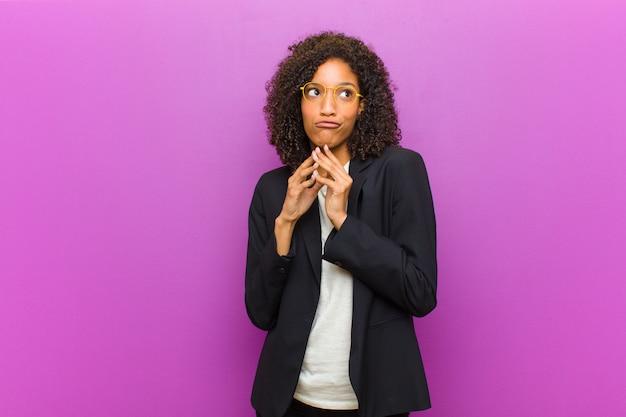 Mulher de negócios preto jovem planejando e conspirando, pensando truques e fraudes tortuosos, astúcia e traição