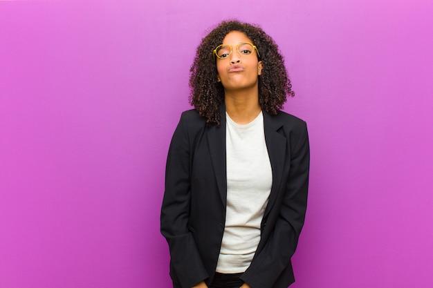 Mulher de negócios preto jovem pressionando os lábios juntos