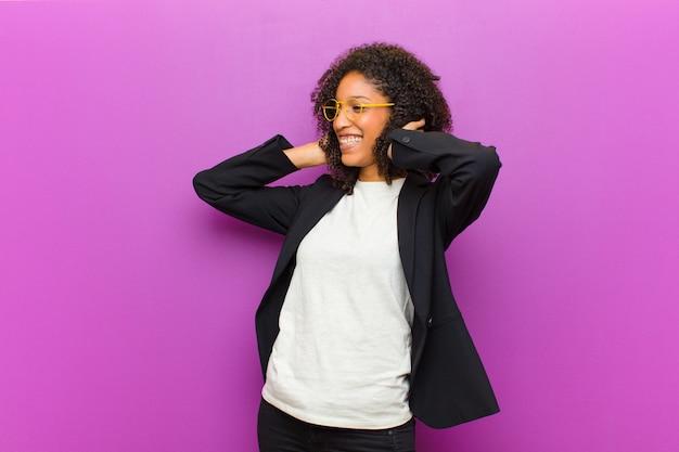 Mulher de negócios preto jovem se sentindo feliz, animado e surpreso, olhando para o lado com as duas mãos no rosto