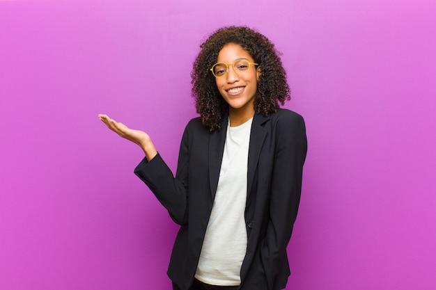 Mulher de negócios preto jovem se sentindo feliz, surpreso e alegre, sorrindo com atitude positiva, percebendo uma solução ou idéia